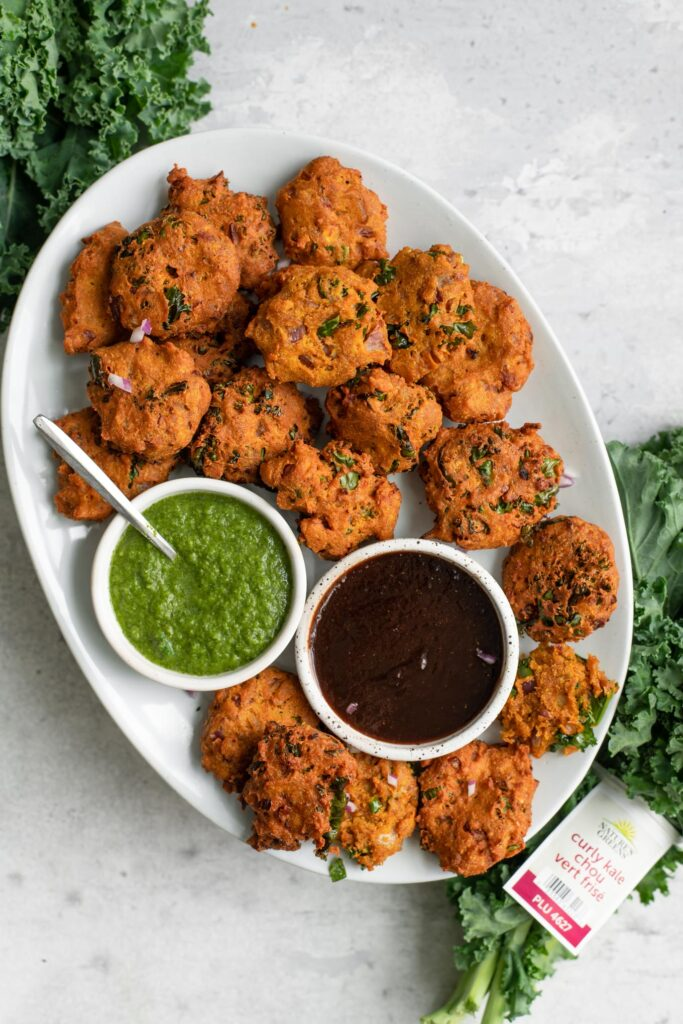 kale pakoras served with tamarind chutney and cilantro chutney with a bunch of nature's greens kale next to the plate