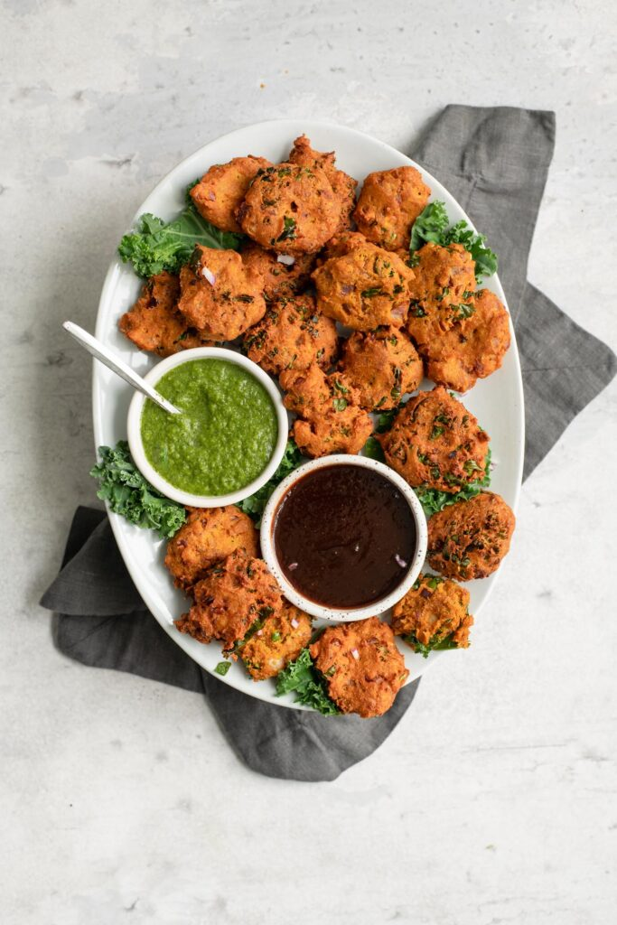 kale pakoras served with tamarind chutney and cilantro chutney on a plate
