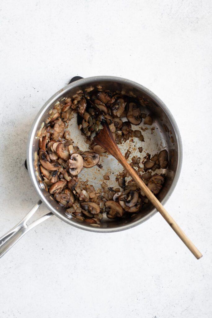 sautéing mushrooms, onion, and garlic in pot