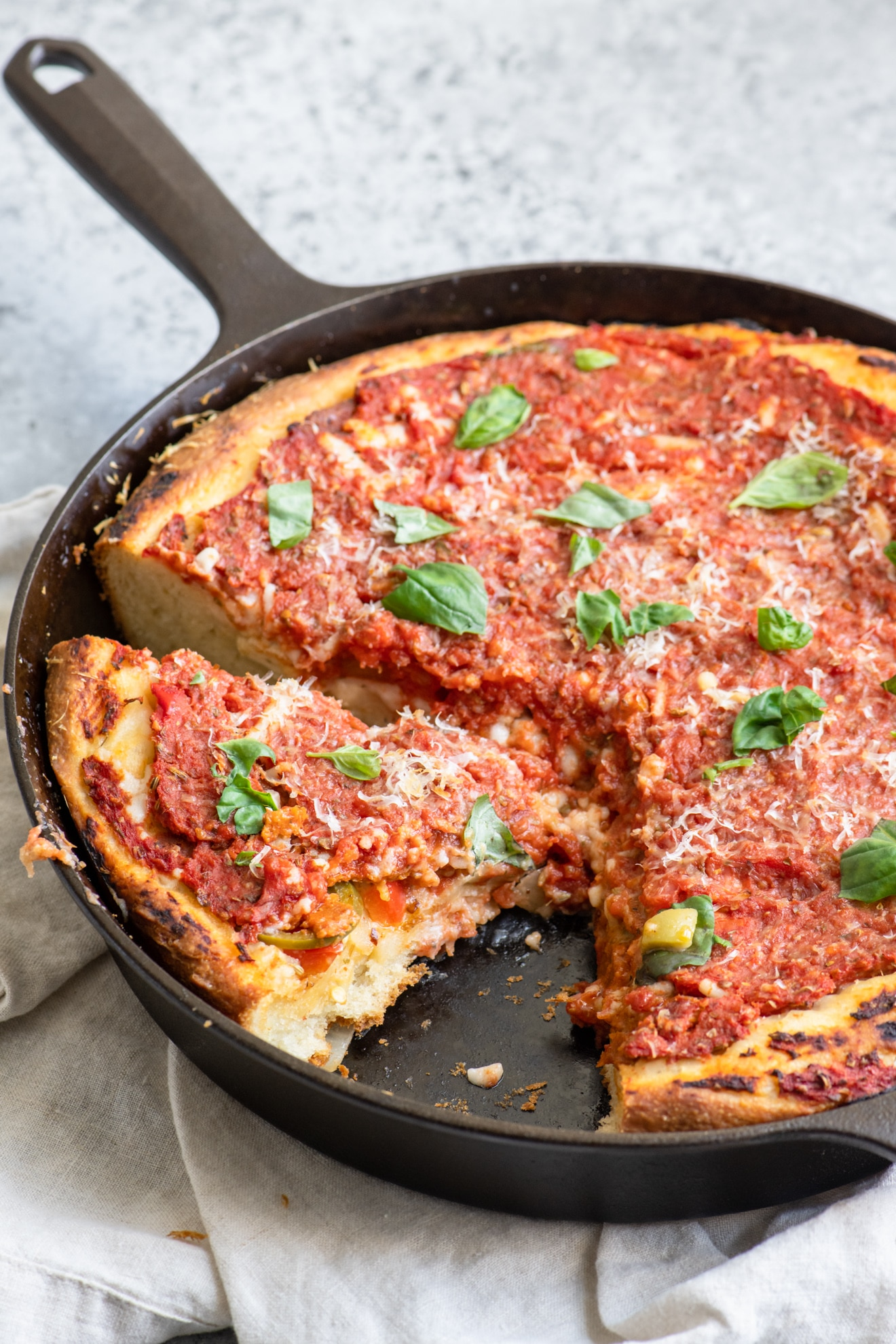 Deep dish pizza with one slice removed and a second cut in the pan