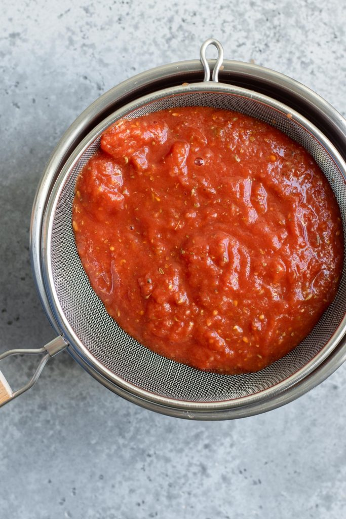 draining tomato sauce in a fine mesh strainer over a mixing bowl