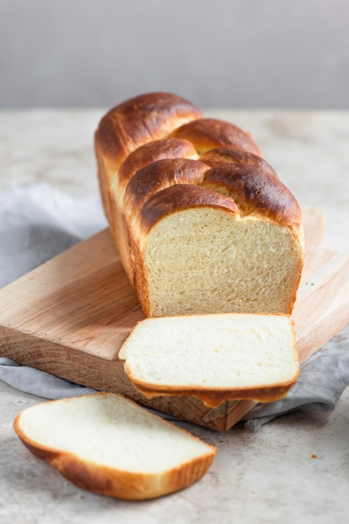 braided brioche loaf with two slices cut off