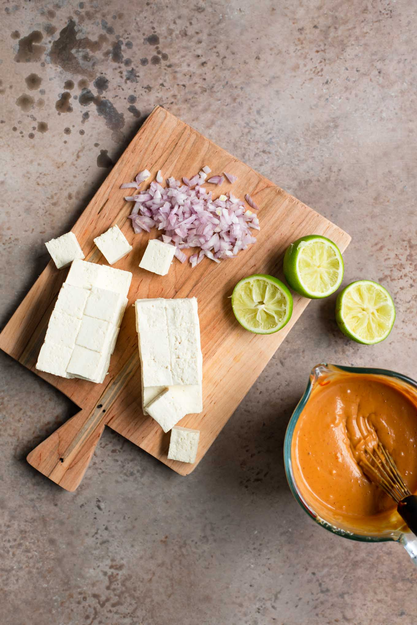 cubed tofu, minced shallot, squeezed lime halves, and peanut sauce