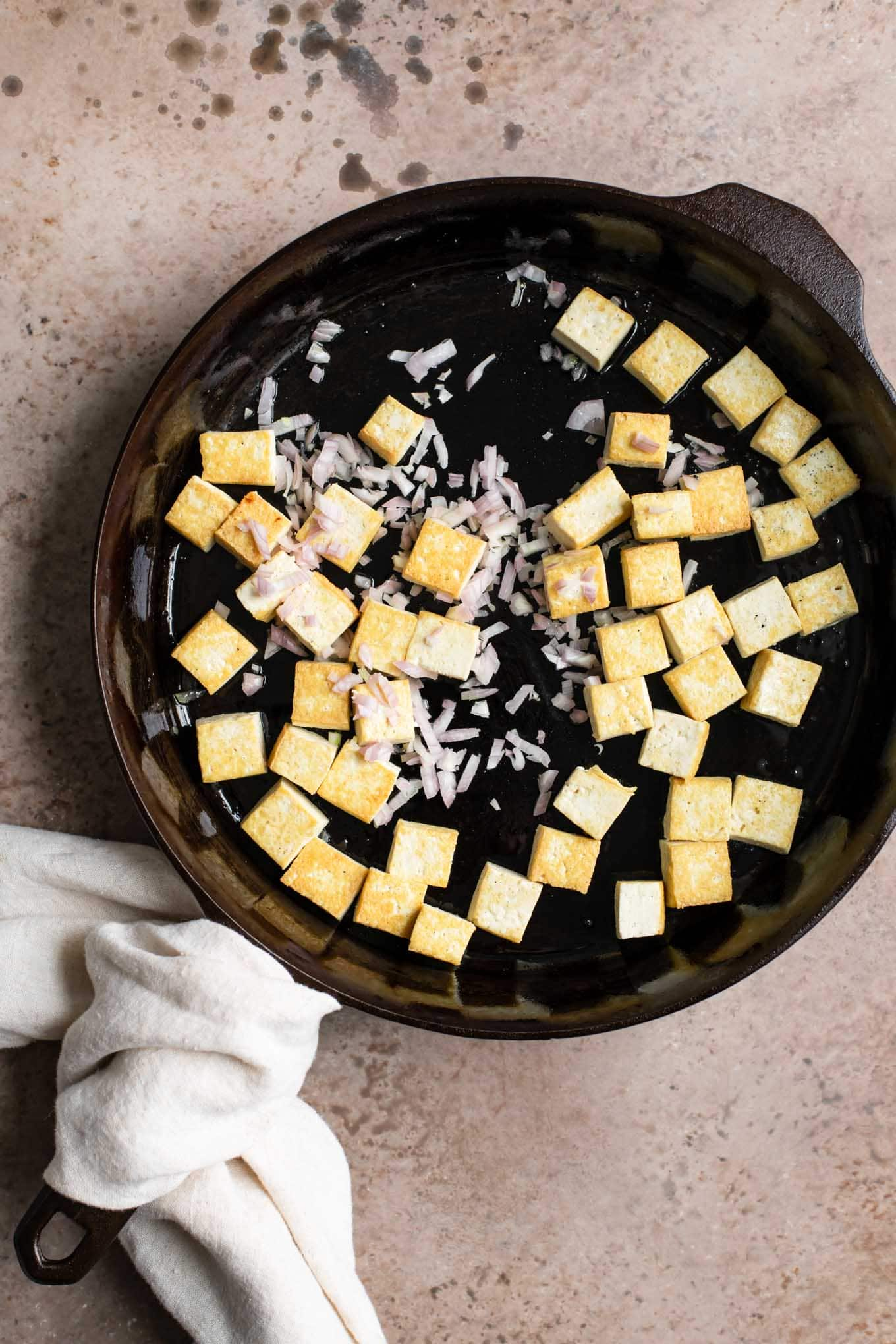 pan fried tofu with shallot added in skillet