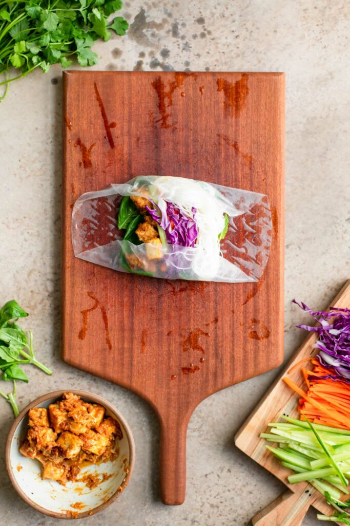 wrapping the spring roll, opposite sides of the wrap are folded in