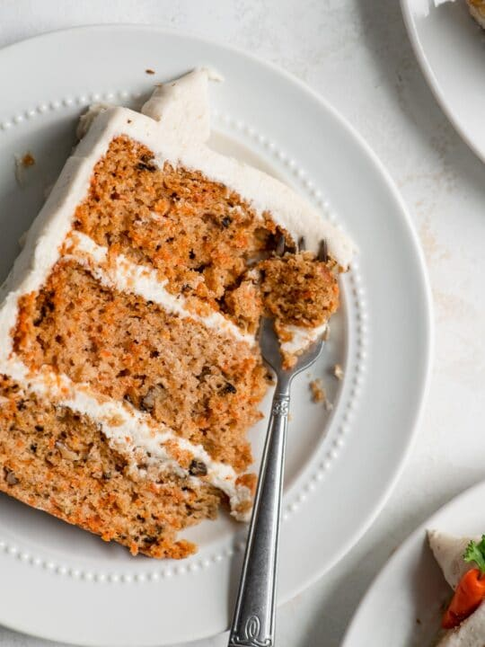 slice of vegan carrot cake on a plate with a fork taking a piece out of the corner