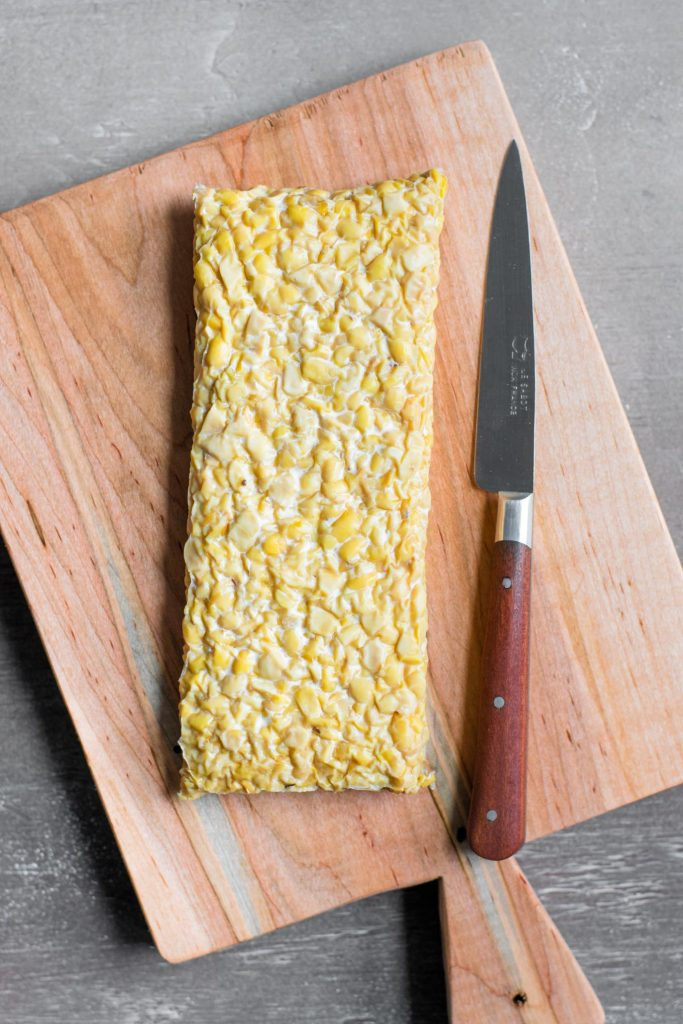 a block of tempeh on a cutting board