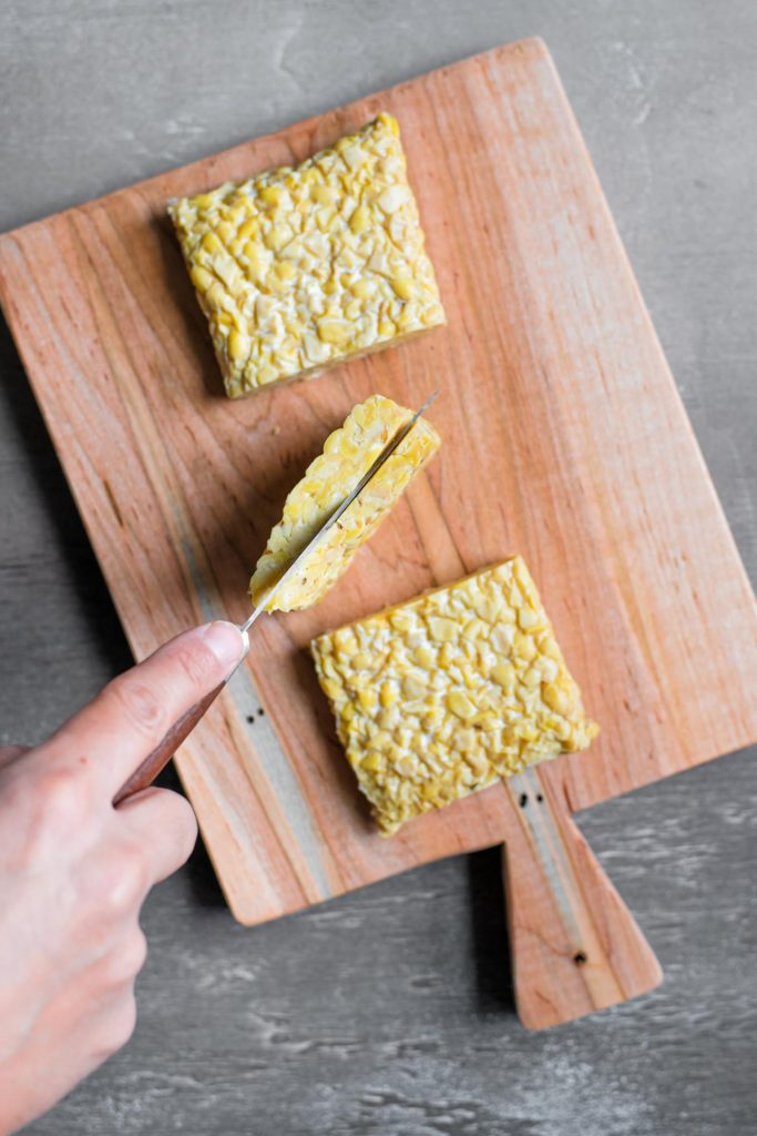 a knife slicing into the middle third of the cut tempeh