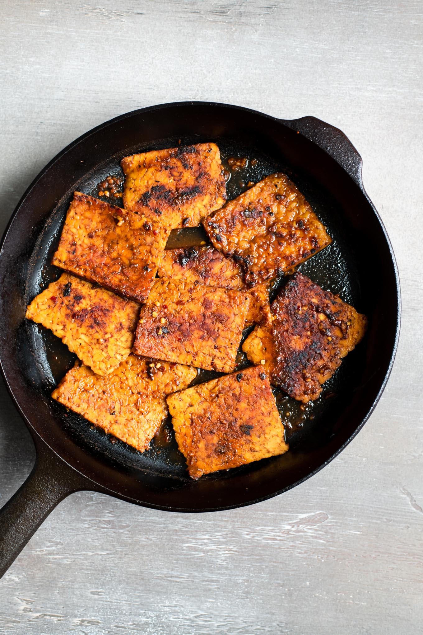 The corned tempeh in the skillet after the marinade is added