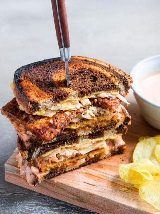 a vegan reuben sandwich cut in half and stacked with a steak knife piercing into the sandwiches