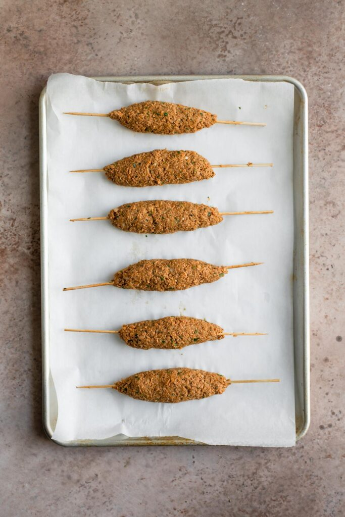 sheekh kababs formed and skewered on a parchment lined baking tray