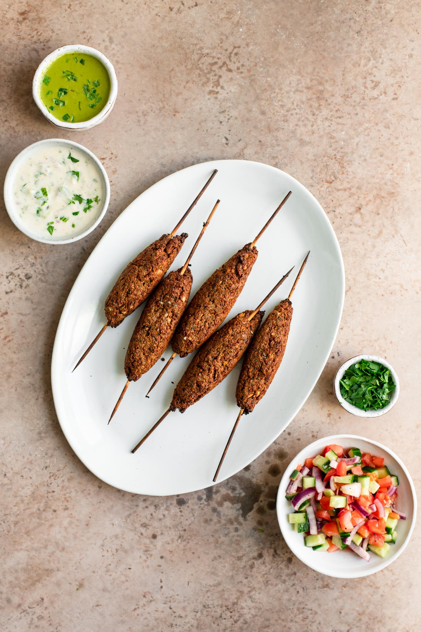 baked vegan sheekh kababs on a plate with sides of chutney, raita, and salad