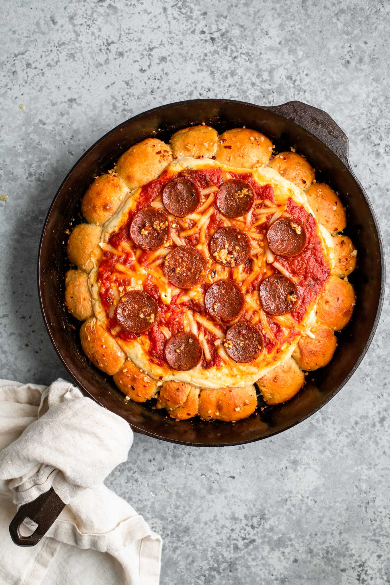 vegan skillet pizza dip served in cast iron skillet with tan linen wrapped around handle