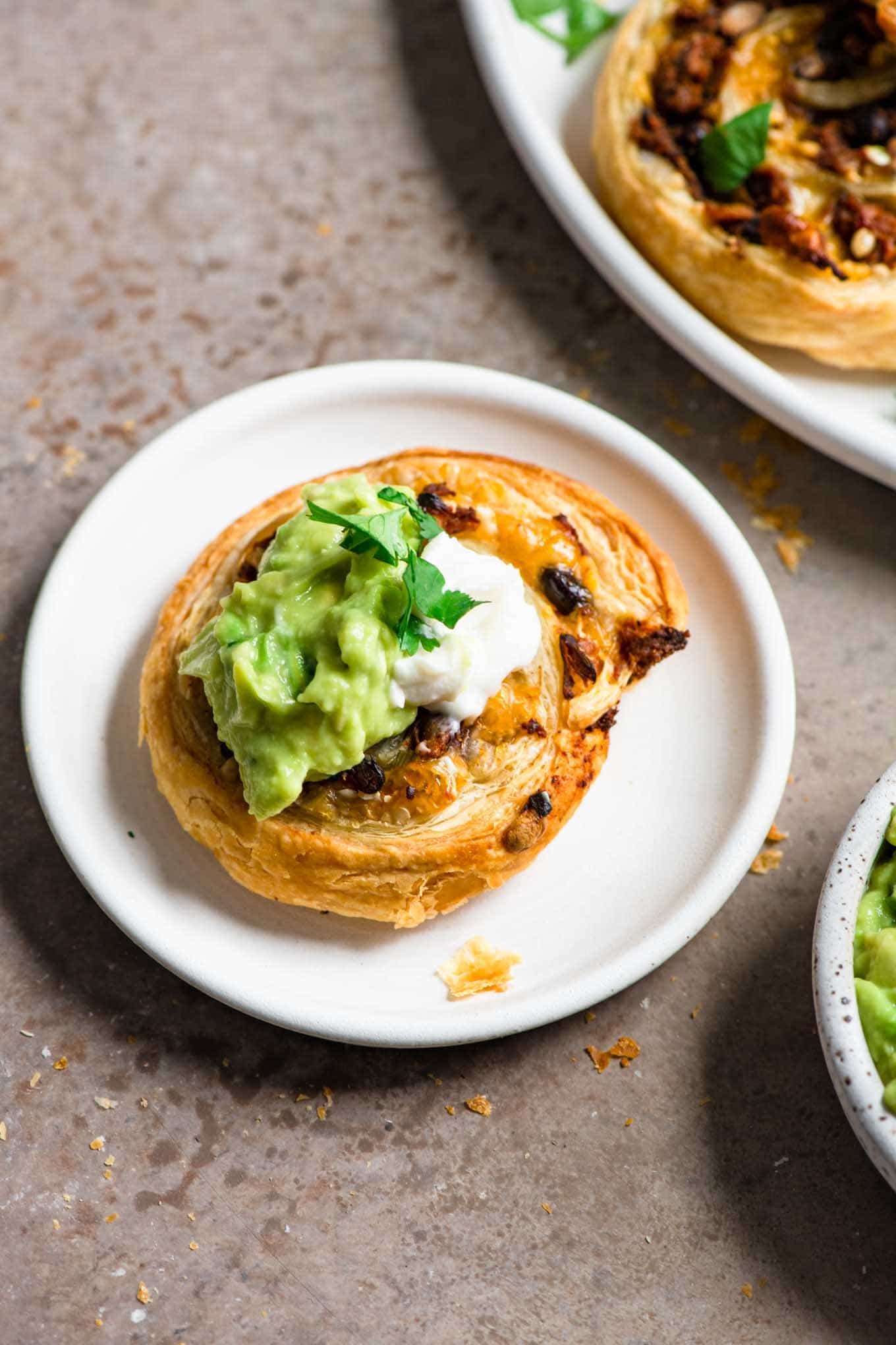 pinwheel topped with guacamole and vegan sour cream