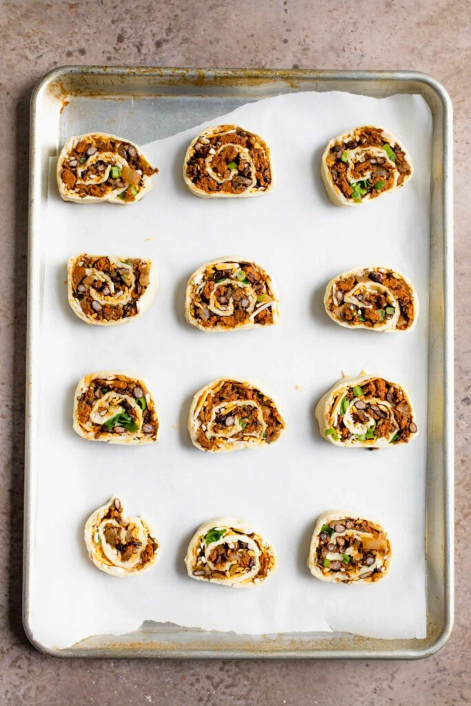 vegan pinwheels on parchment lined baking tray before baking