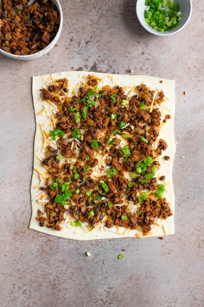 scallions on top of the bean and cheese on the puff pastry