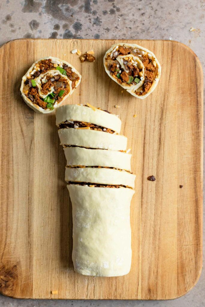 vegan pinwheel roll on cutting board with 6 slices, two resting flat