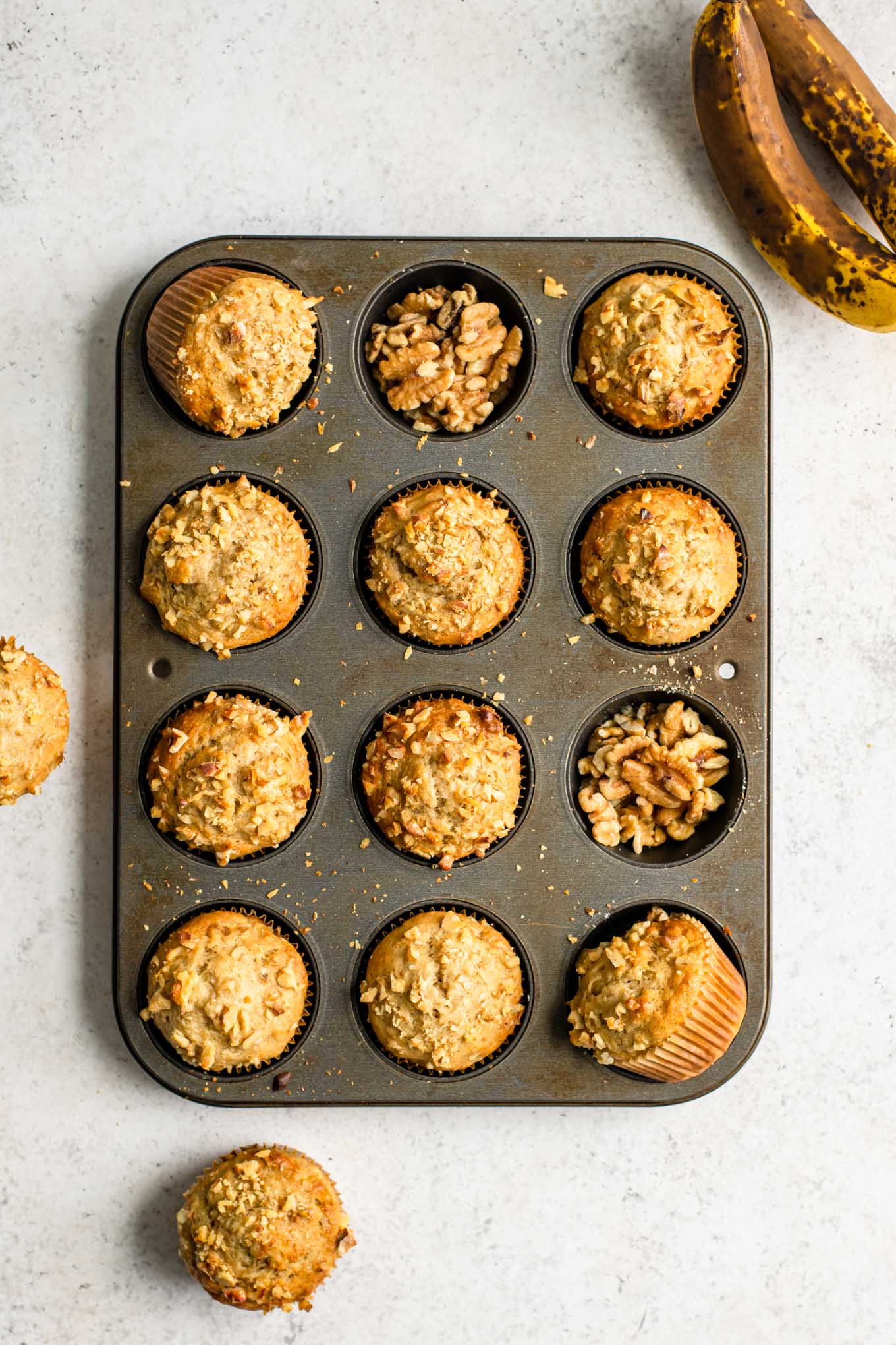 baked banana nut muffins in a muffin pan with two of the muffin wells filled with walnuts