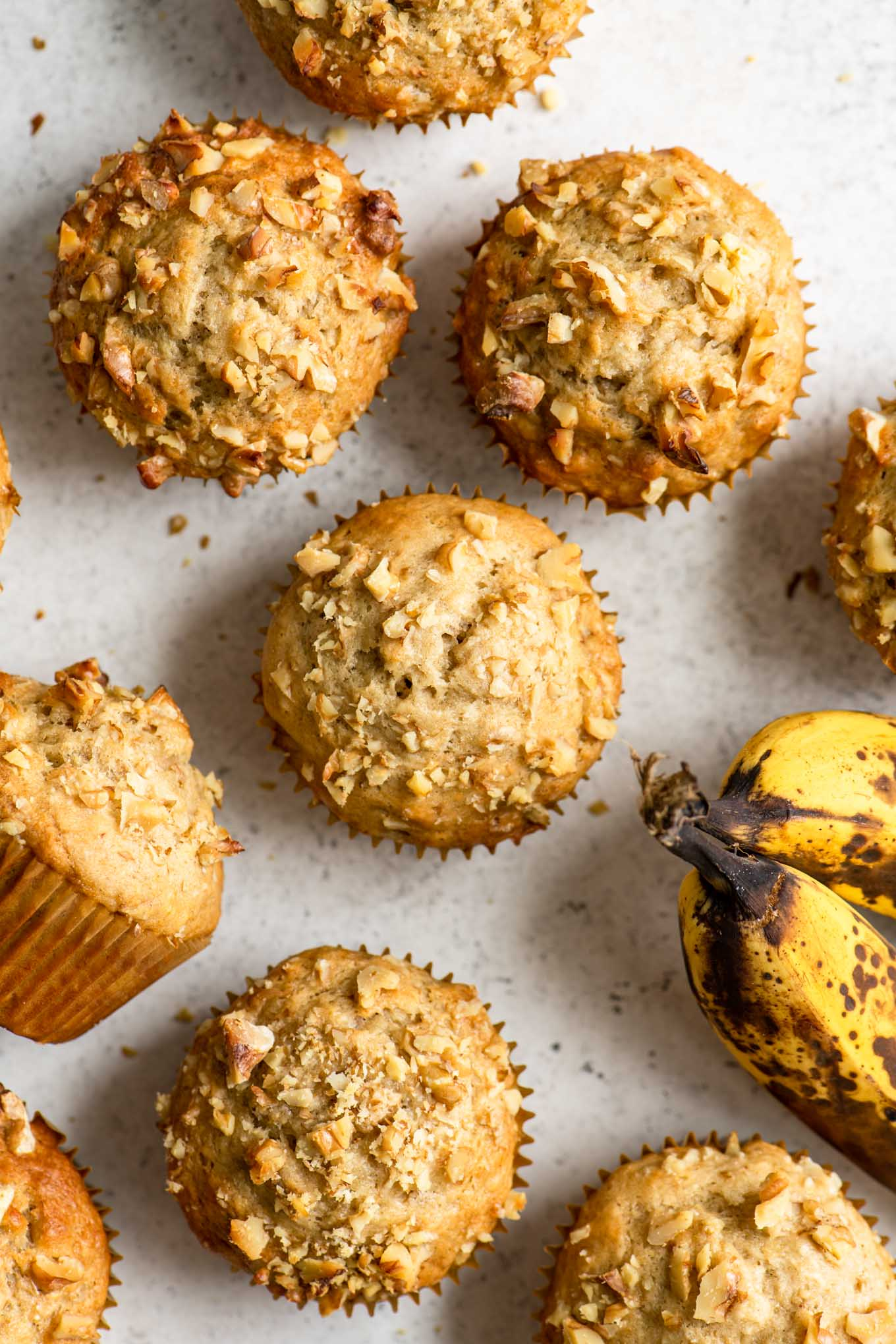 overhead of vegan banana nut muffins with two ripe bananas peeking in the side