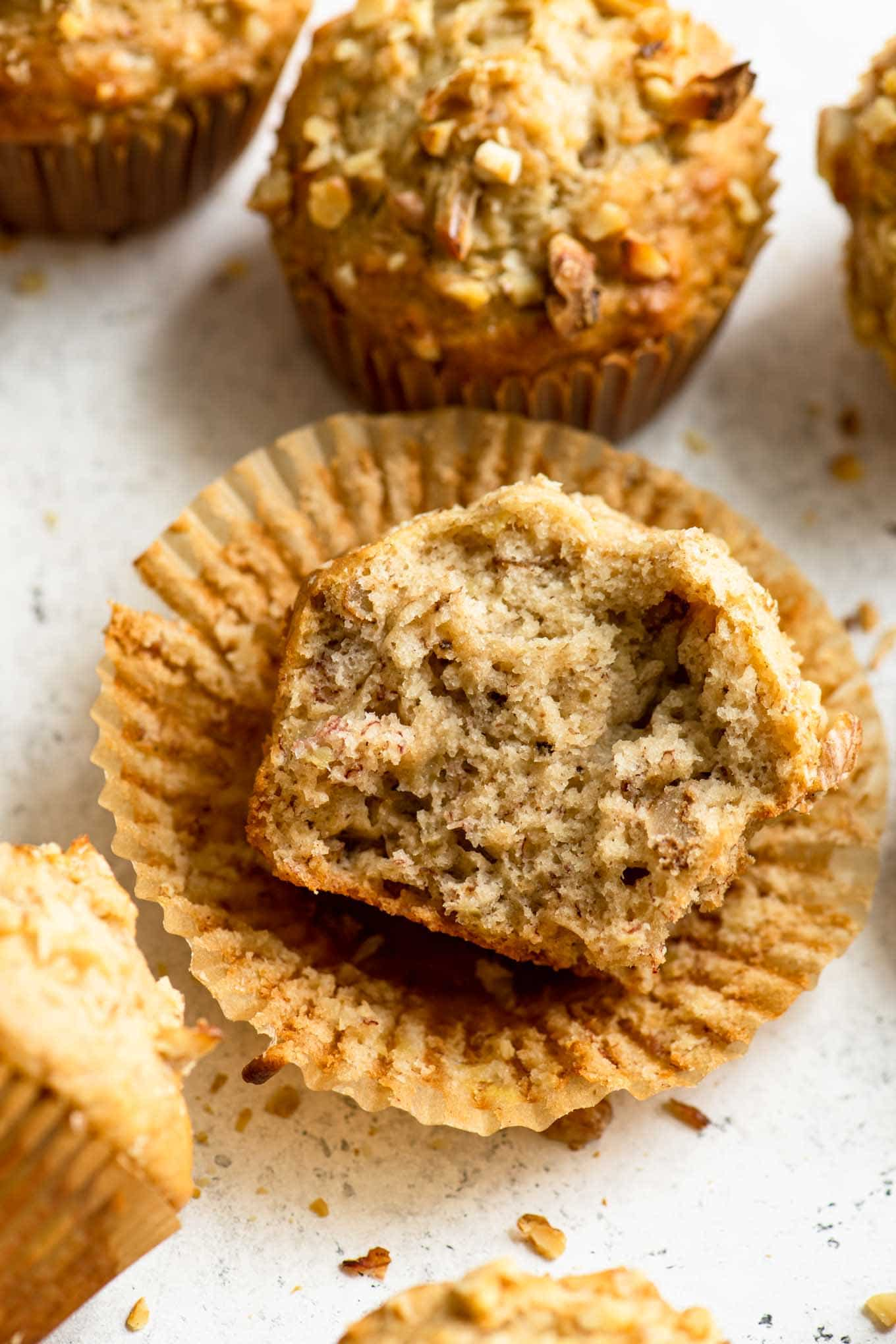 angled view of vegan banana nut muffin unwrapped and broken in half to show the soft crumb