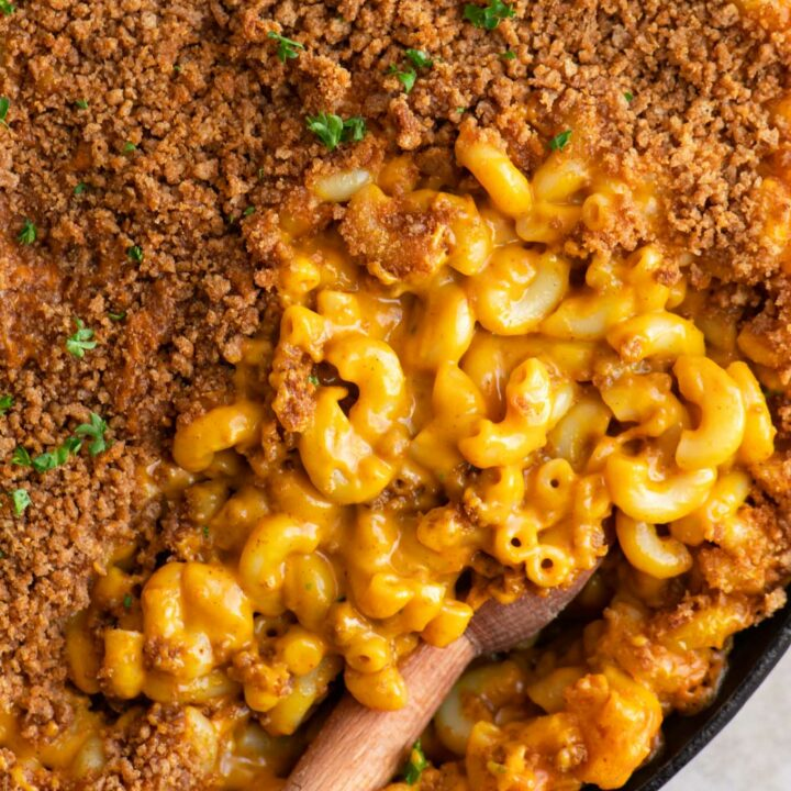 close up of vegan berbere mac and cheese with half of it covered with injera crumb topping and other half showing the cheesy noodles
