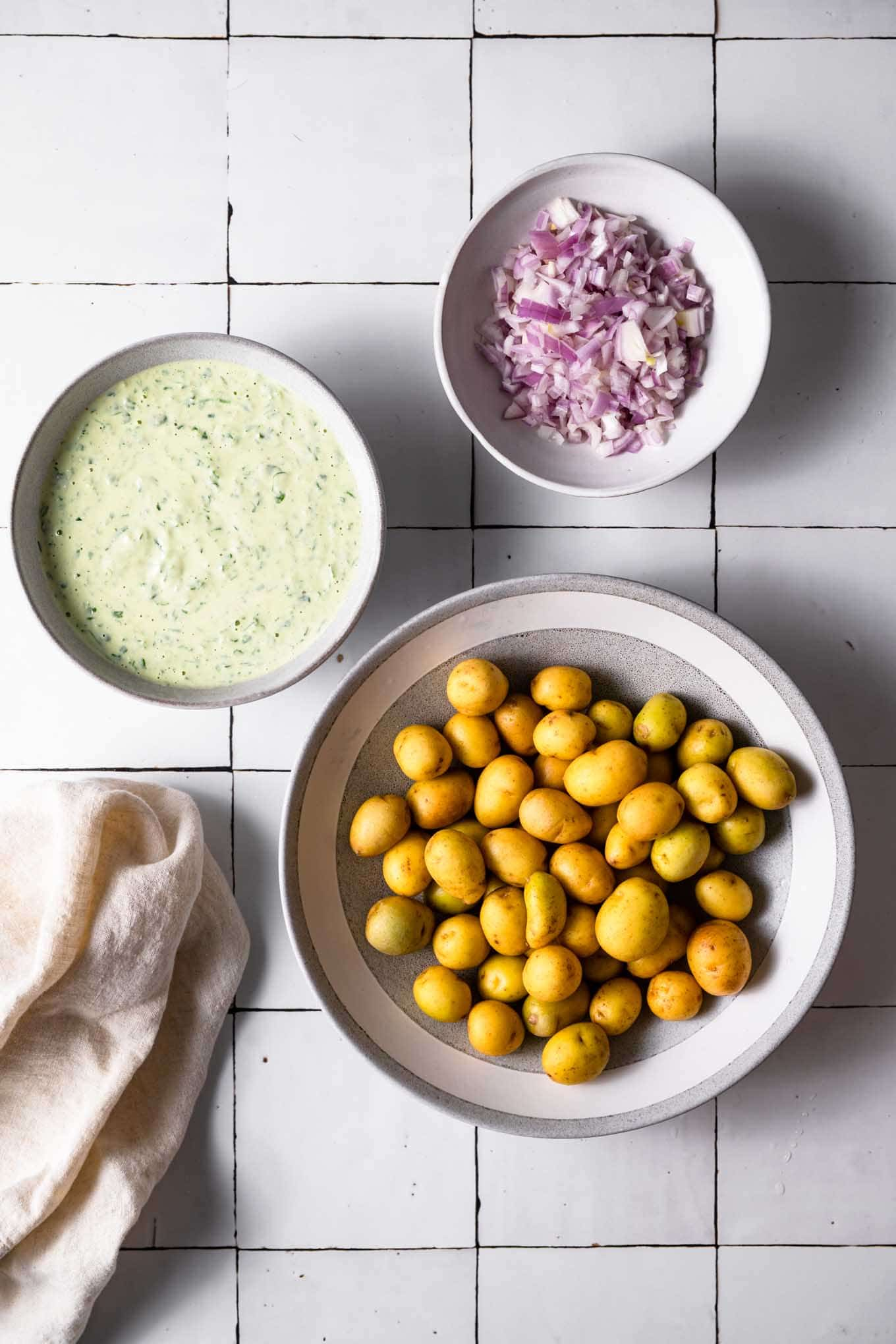baby potatoes, dressing, and minced shallot in bowls