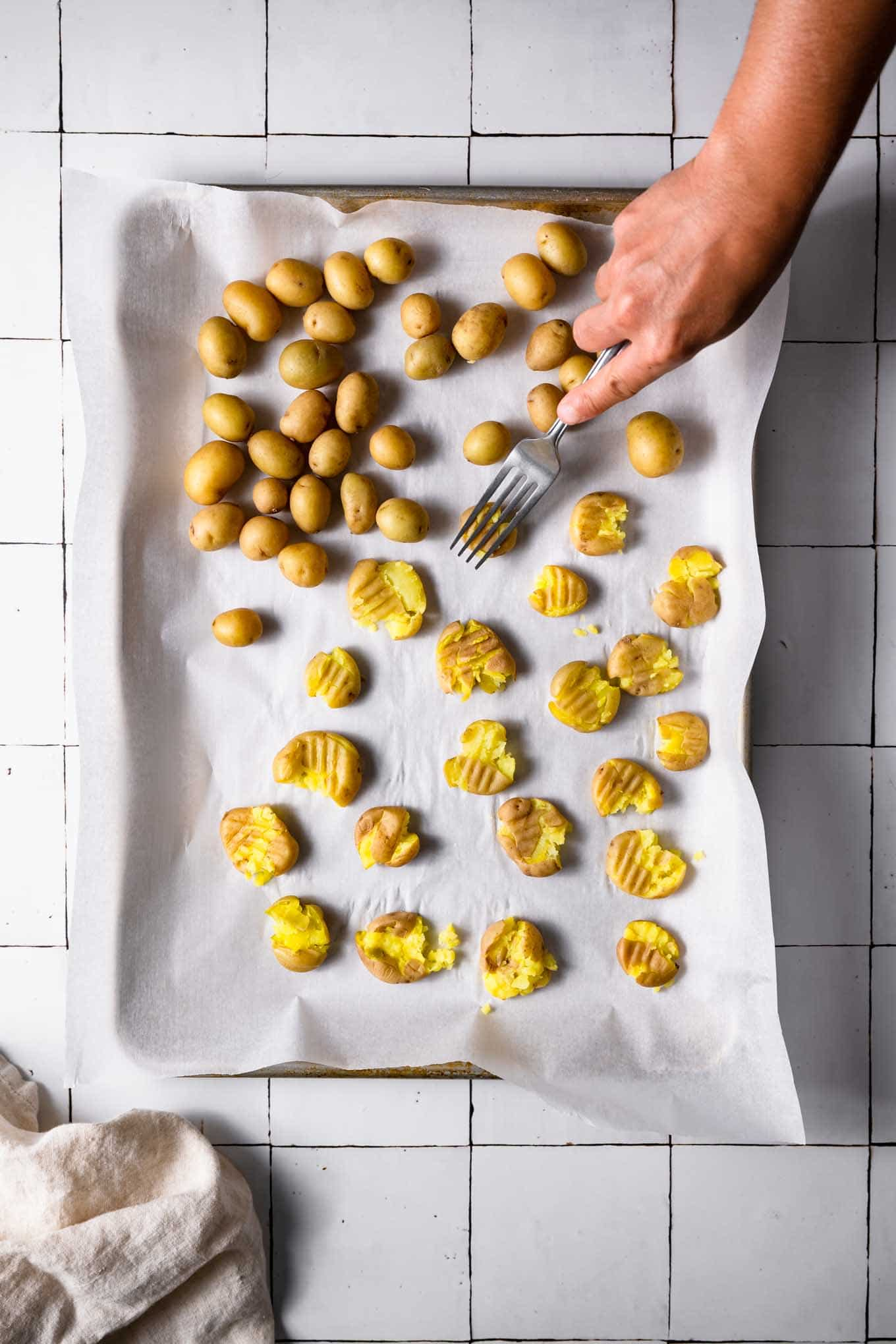 smashing boiled baby potatoes on baking tray