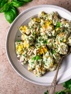 herbed smashed potato salad in bowl with basil and parsley sprigs in edge of photo