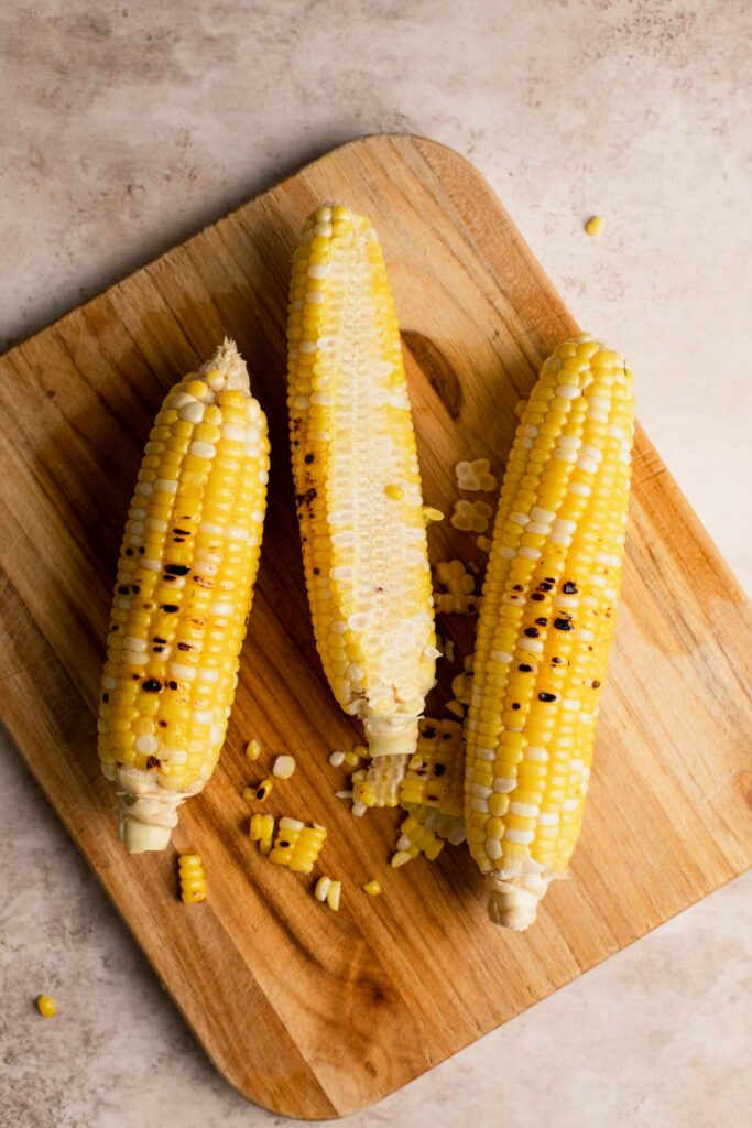roasted corn on the cob on a cutting board with kernels cut off one side of one cob