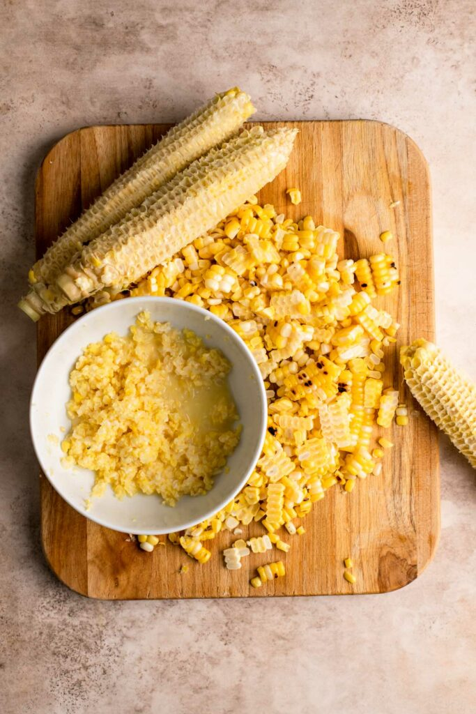 corn cut off cobs on cutting board with bowl full of kernels and juice scraped off cobs