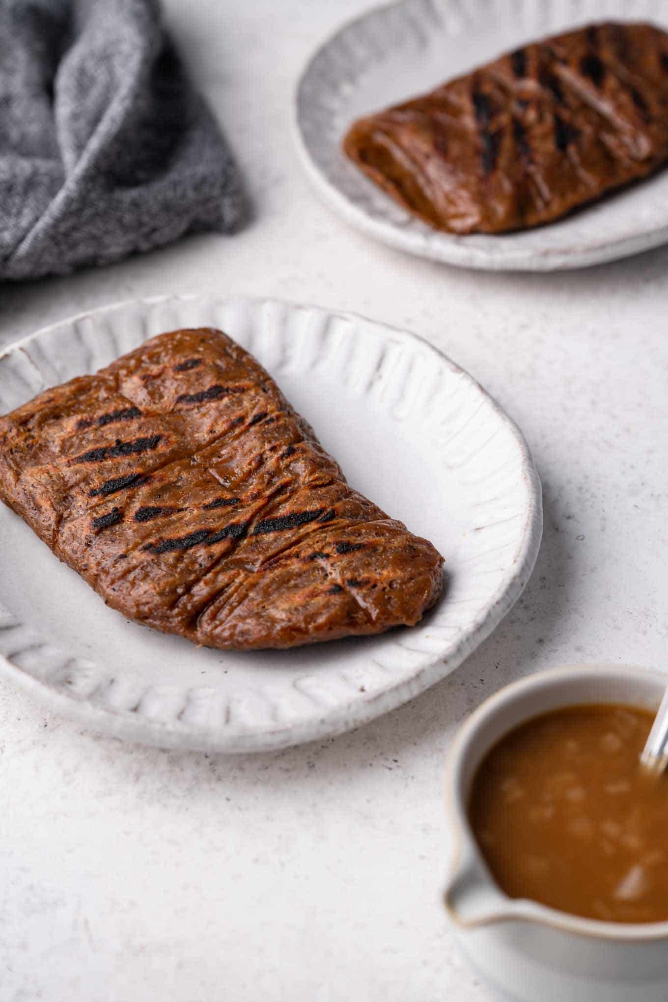 grilled seitan steaks on plates with a side of gravy