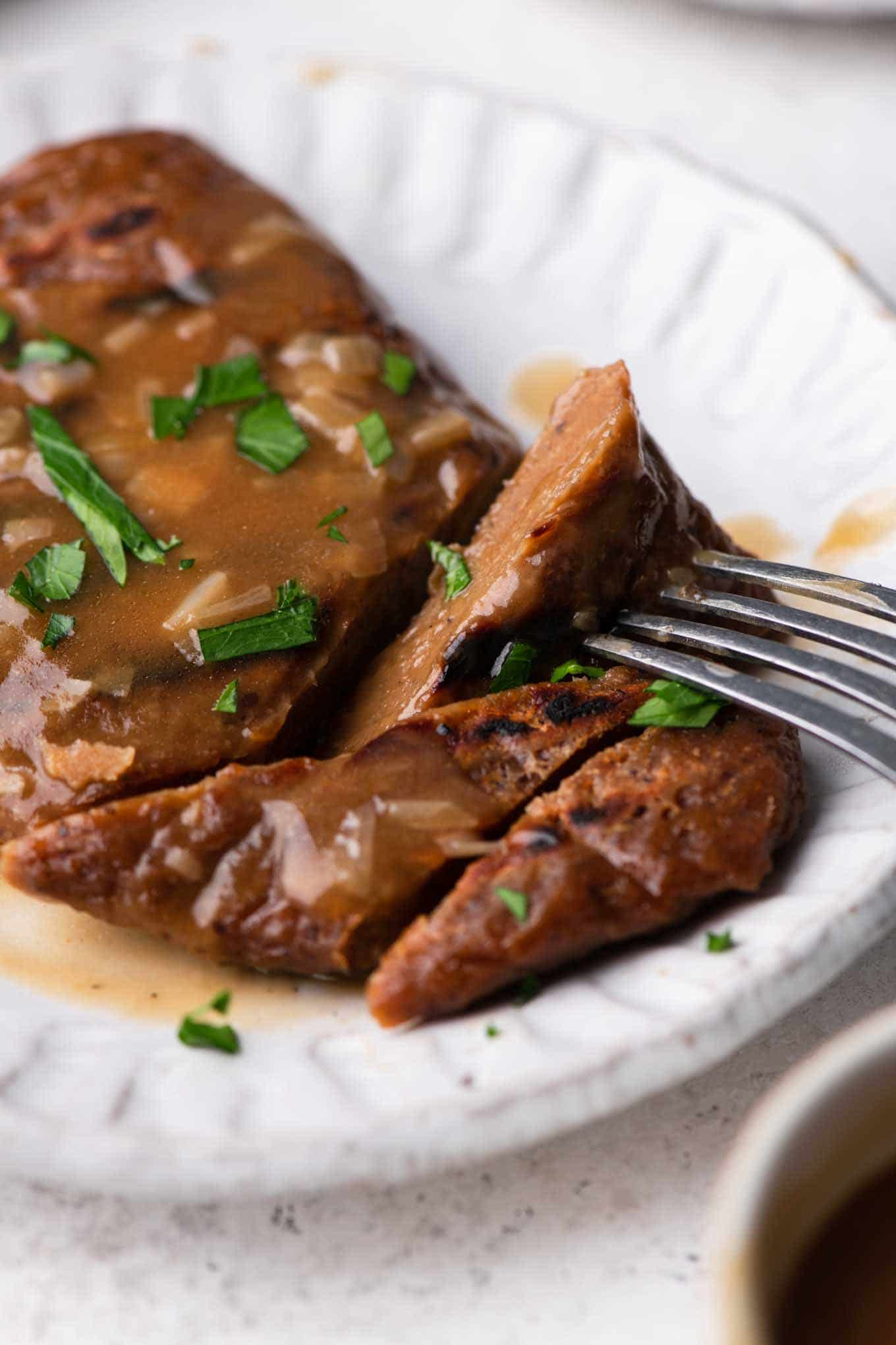 seitan steak topped with gravy and parsley with some bites cut and one on a fork
