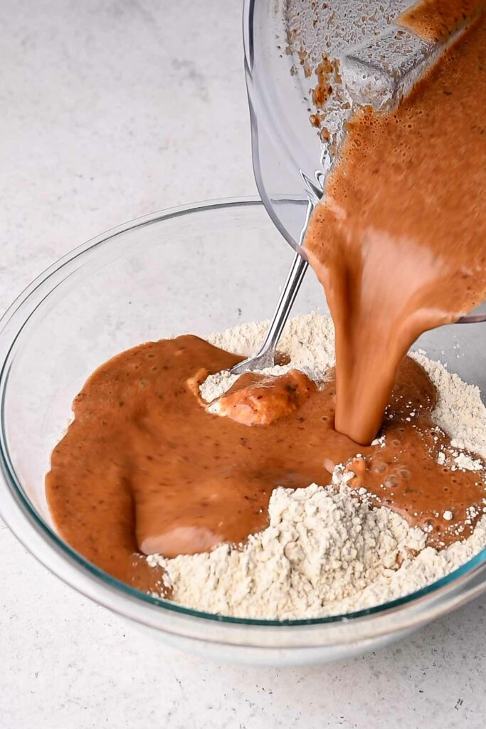 pouring blended wet ingredients into wheat gluten and chickpea flour