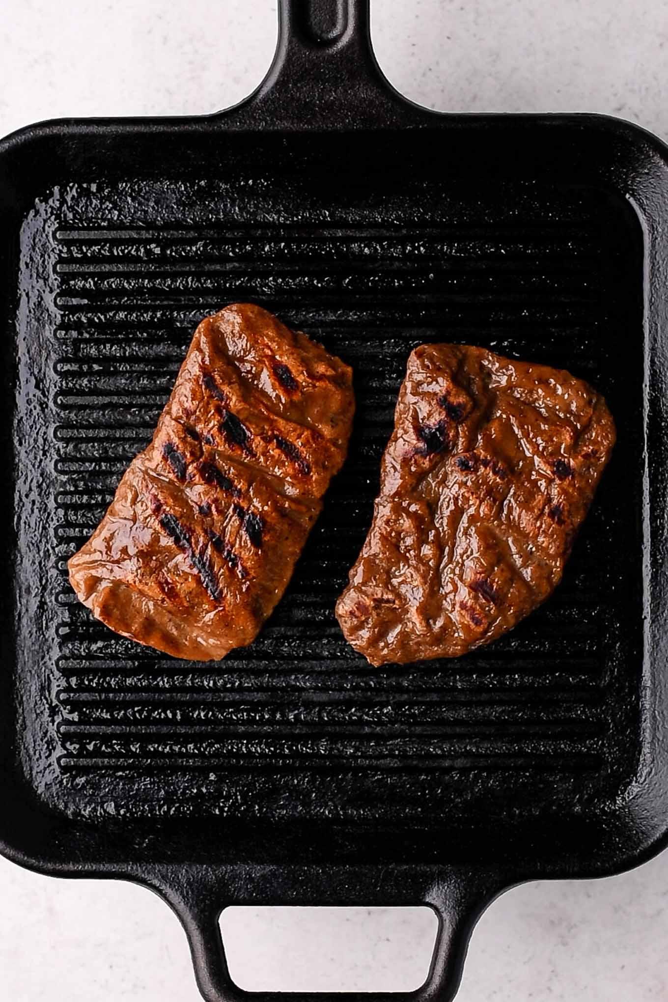 two seitan steaks on grill