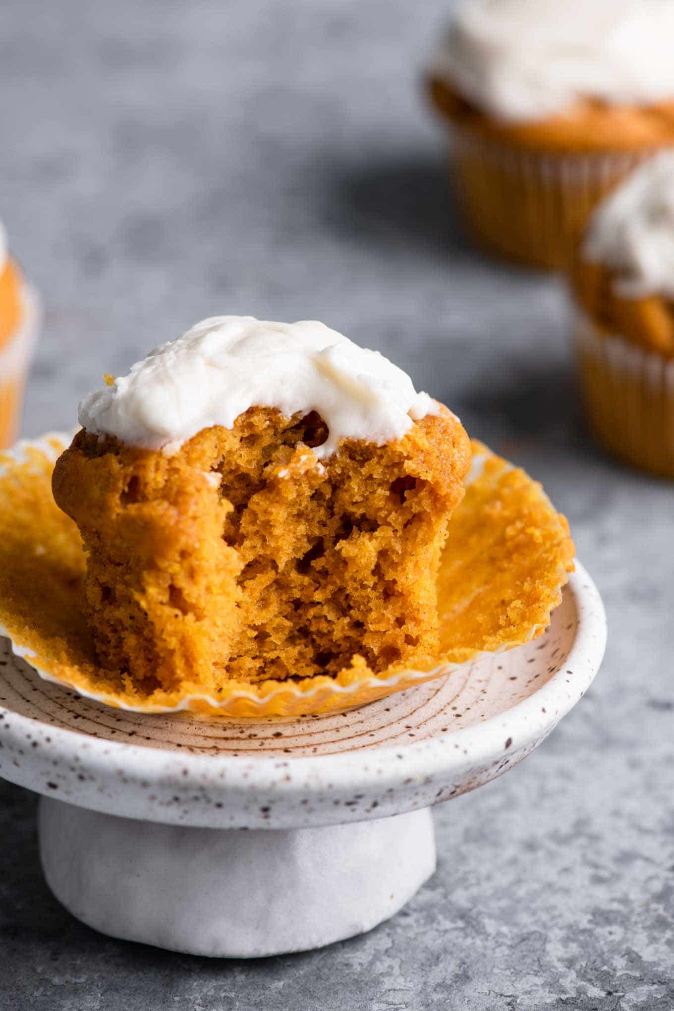 vegan pumpkin muffin with bite taken out on a mini cake stand