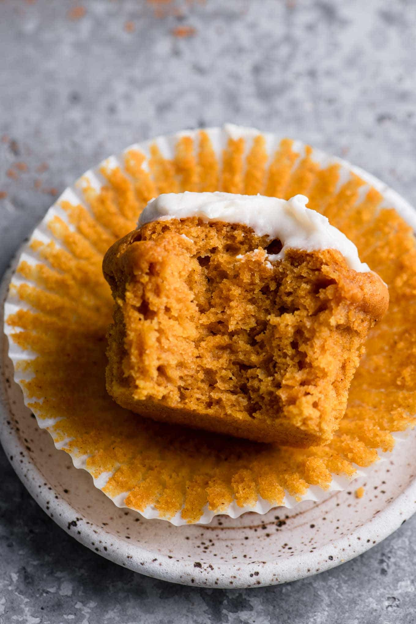 cream cheese frosted vegan pumpkin muffin with bite taken out