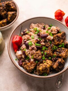 Jamaican jerk tempeh served with red beans and rice in a bowl with a small bowl of jerk tempeh on the side